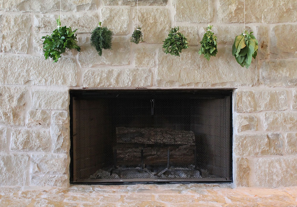 Hanging herbs to dry over the fireplace